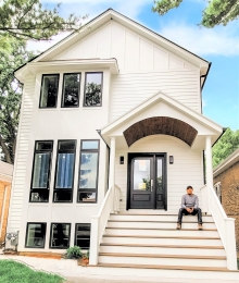 Sergio Balderas sitting on the front of his newly constructed home in North Riverside, IL.